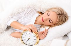 Good morning attractive young woman. Soon to wake up for sleeping attractive young woman with alarm clock Stock Photos