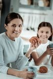 Beautiful lady eating croissants with her daughter stock photography