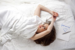Good morning beautiful woman. Top view of a young beautiful woman, in the white linen  bed with love letter Good morning Royalty Free Stock Images