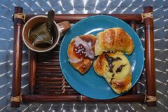 Good morning breakfast concept, tea on tray with croissants and