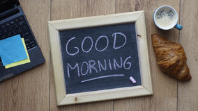 Good morning breakfast. Good morning written on a chalkboard next to a breakfast at the office Royalty Free Stock Photo