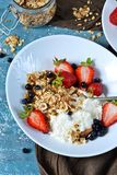 Good morning! Breakfast with yoghurt, granola and strawberries o. N a blue, concrete background stock images