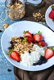 Good morning! Breakfast with yoghurt, granola and strawberries o. N a blue, concrete background royalty free stock image