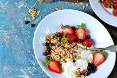 Good morning! Breakfast with yoghurt, granola and strawberries o. N a blue, concrete background stock image