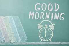 Good morning!. Chalk drawing of books, alarm clock and writing wish. Education concept Stock Image