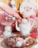 Good morning. Chocolate muffin dusted with icing sugar with a pink rose in the center with hands on a silver tray on a background tea set Stock Image