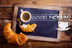 Good morning with coffee and a croissant. Good morning sign with a cup of fresh hot morning coffee and a broken croissant on an old school slate with a Stock Images