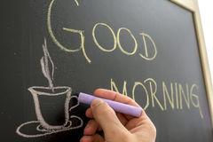 Good morning coffee cup. Closeup of cafe owner writing good morning sign on black board Royalty Free Stock Photography