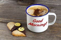 Good Morning with Coffee and Smiley Cookies. Enamel Mugs with hot Coffee and two Cookies in Heart Shape on a rustic wooden board with the Word Good Morning on Stock Image