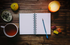 Good Morning Concept. Notebook, cup of tea and other elements on wood table Stock Image