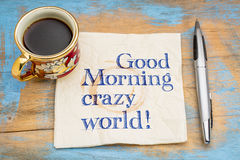 Good Morning crazy world!. Good Morning crazy world - handwriting on a napkin with a cup of espresso coffee royalty free stock image