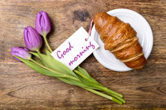 Good morning. Croissant, purple tulips and card with good morning written on wooden table top view Stock Images
