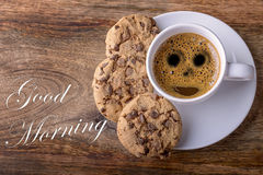 Good morning. Cup of coffee with chocolate cookies on wood and good morning written Stock Image