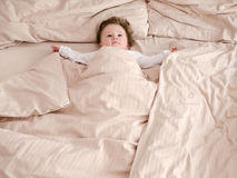 Good morning. Cute hairy baby spreading arms in the bed Royalty Free Stock Images