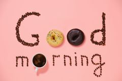 Good morning, donuts and coffee. A cup of good morning coffee with donuts and grains on a pink background top view stock photos