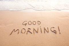 Good morning. Message text concept card, text written on sand beach royalty free stock image