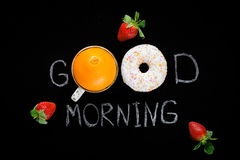 Good morning greeting on chalk board. Healthy food, fresh fruits. Good morning greeting written on black chalk board. Donut (doughnut), sweet orange and Stock Images