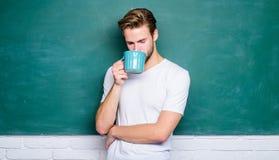 Good morning. Handsome man enjoy hot coffee. Coffee addicted. Inspiring drink. Dose of caffeine. Teacher drink coffee. Chalkboard background. Sip recharging royalty free stock photography