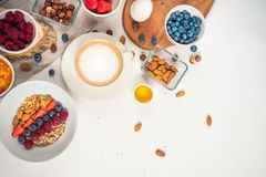 Good morning - healthy breakfast background with oatmeal coffee, berries, egg, nuts. White wooden food background, top view stock image