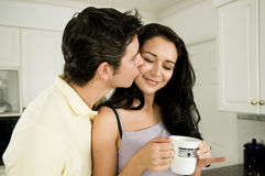Good Morning and a Kiss!. An attractive couple enjoys the morning with a kiss and a hot cup of coffee or tea Royalty Free Stock Images