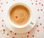 Good morning with love. Cup of coffee on the white background with little red hearts and wedding ring in blur Royalty Free Stock Image