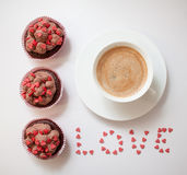 Good morning with love. Sweet homemade cupcakes with chocolate cream and decorated little pink sugar hearts, cup of coffee and word love Stock Images