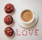 Good morning with love. Sweet homemade cupcakes with chocolate cream and decorated little pink sugar hearts, cup of coffee and word love Royalty Free Stock Photography