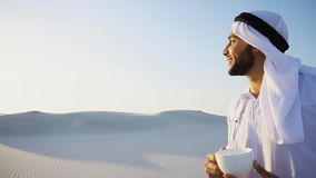 Good morning for male sheikh in middle of huge desert over cup o. Handsome male Arab tastes coffee drink from white cup and enjoys peaceful morning, smiling and Stock Photo