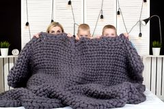 Good morning! Mother and two small sons hide under a knitted blanket. Positive awakening. royalty free stock photo