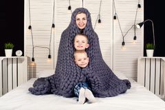 Good morning! Mother and two small sons hide under a knitted blanket. Positive awakening. royalty free stock images