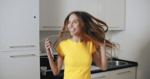 Good Morning with Music. Happy young girl dancing in the kitchen while listen to the music on smartphone stock video footage