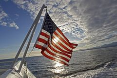 Good Morning Old Glory. American Flag flies on a Stern of a boat on the water stock image