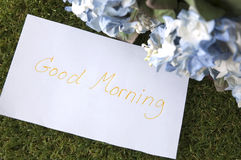 Good morning on paper note. Close up good morning on paper note with flowers Stock Photos