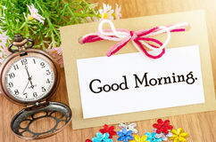 Good morning on paper tag. And libbon and pocket watch wite pink flower on wooden background Stock Photography