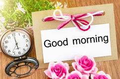 Good morning paper tag. And pocket watch with pink rose on wooden background Royalty Free Stock Photography