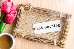 Good morning paper tag. Good morning paper tag in sack photo frame and coffee with red tulip on wooden background Stock Images