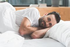 Joyful guy awakes in comfortable bed. Good morning. Portrait of happy young man waking up with joy. He is looking at camera and smiling Stock Photography