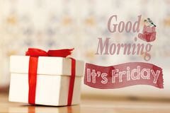 Good morning it`s friday message with white gift box with red ribbon on wood background. Good morning it`s friday message with white gift box with red ribbon stock photo