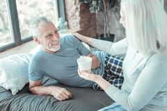 Satisfied unshaken man lying and taking a cup. Good morning. Satisfied unshaken aged men lying on the bed smiling and taking a cup which bringing his wife Stock Photography