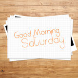 Good Morning Saturday. On paper and Brown wood plank background Royalty Free Stock Images