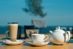 Good morning. set of latte mugs, a Cup of tea and a teapot with cane sugar on the summer terrace of the cafe royalty free stock photography