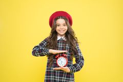 Good morning. Small child smiling in morning on yellow background. Happy little girl holding alarm clock early in the. Morning. Waking up in morning stock photo