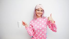 Good Morning. Smiling young woman shows thumb up. Girl in pink pajamas and sleep mask. On white background stock image