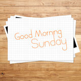 Good Morning Sunday. On paper and Brown wood plank background Stock Images