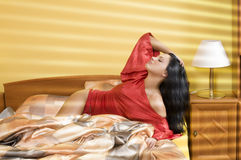 Good morning sunshine. Sensual brunette with red nightgown and black hair enjoing the morning sunshine Stock Image
