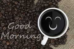 Good morning text in coffee cup on coffee beans background Royalty Free Stock Photo