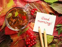 Good morning - the text on a white card and a cup of tea with herbs and berries on a surface with bright autumn leaves. Royalty Free Stock Image