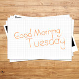 Good Morning Tuesday. On paper and Brown wood plank background Stock Image