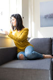 Good morning! Wanna pass by? Woman relaxing on couch and making a phone call Stock Image