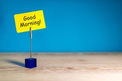 Good morning - wish for a good day. Note at yellow paper at blue background. With empty space for text, mockup and royalty free stock photography